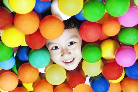 playcentre: Happy asian boy playing with colorful balls, shot at playground
