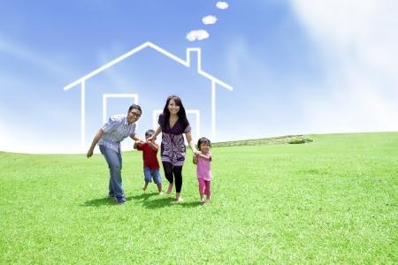 Gelukkige familie die op gebied met een getrokken huis op achtergrond loopt Stockfoto