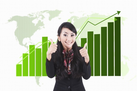 good investment: Cheerful success businesswoman showing thumbs-up. shot over business chart background Stock Photo