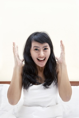 Cheerful young asian woman laughing in bedroom Stock Photo - 14684373