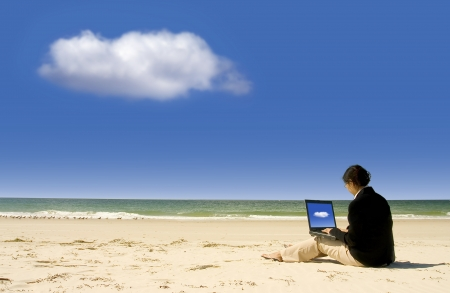 Cloud Computing: businesswoman with business suit working at the beach photo