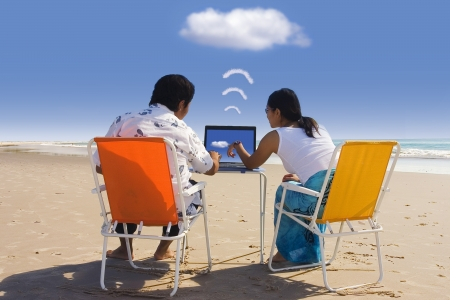 wifi: Cloud computing: Casual Workers having a business meeting at Beach Stock Photo