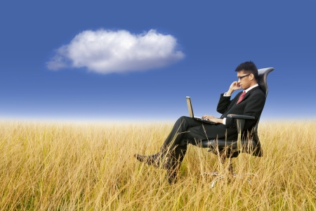 Cloud networking: businessman working with laptop photo