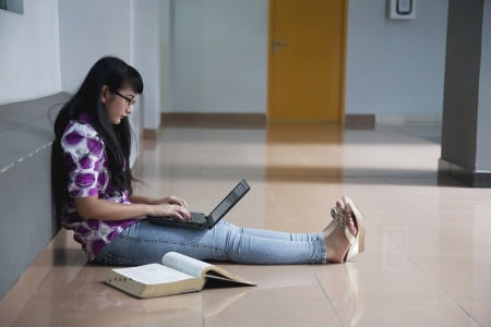 Female accounting student studying with laptop computer and textbook in campus aisle photo