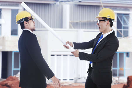 rival: Business disagreement: an engineer hit his rival using blueprints shot at workplace outdoor Stock Photo