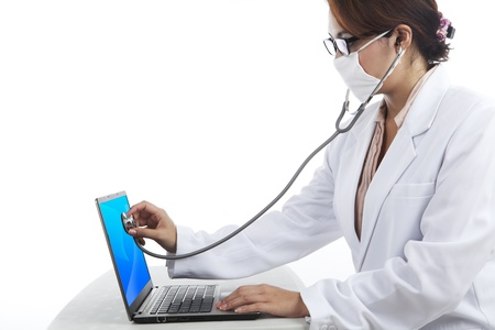 Shot of young woman in lab coat  checking laptop with stethoscope photo