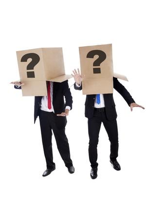 persona confundida: Dos hombres de negocios confusos con signo de interrogación sobre el cartón encontrar el camino Foto de archivo