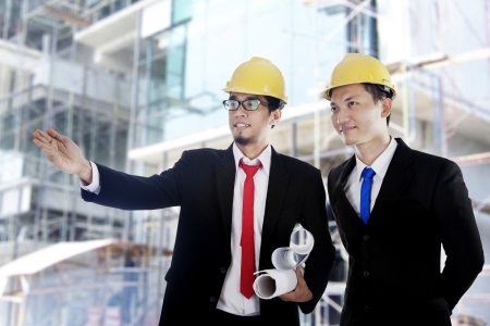 constructors: Two Asian businessmen with blueprint at construction site  Stock Photo