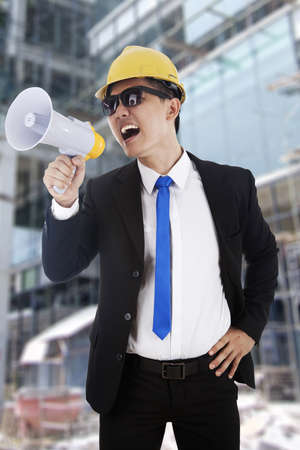 Angry construction manager screaming using a megaphone photo