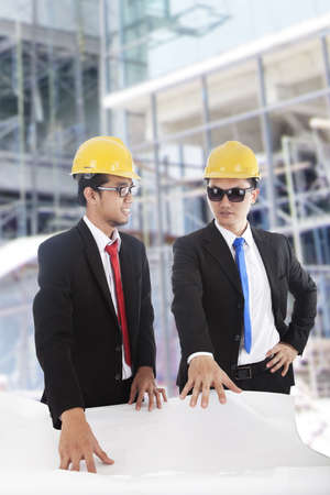 Two Asian businessmen duscussing the blueprint at construction site  photo