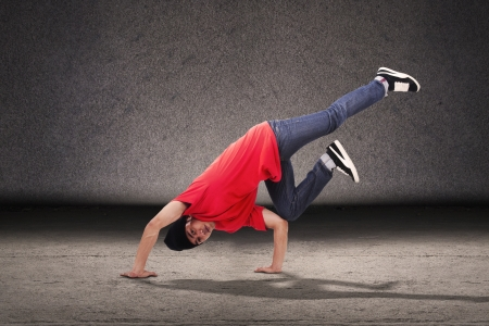 Young breakdancer doing a breakdance style in front of grey background photo