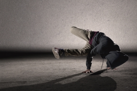 hand on hip: Cool looking dancer breakdancing on grey grunge wall background Stock Photo