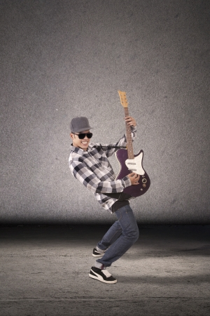 Cool guitarist playing guitar in front of dark background. shot in studio photo