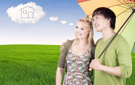 droomhuis: Portret van jonge gemengde paar onder veelkleurige paraplu te kijken naar droomhuis op de wolk