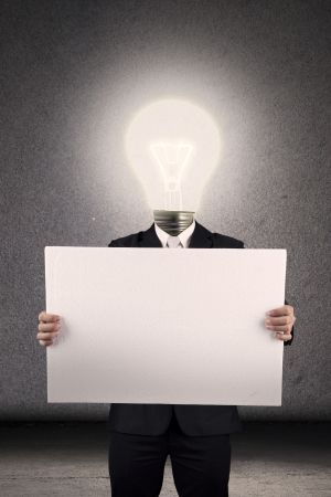 Businessman with head made of lightbulb holding blank white board as a copy space photo