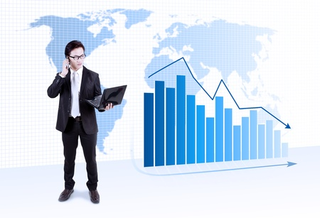 Businessman holding laptop with a world map and graph with arrow pointing downward financial crisis  photo