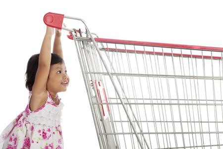 shopping trolleys: Cute little asian girl pushing trolley shot in studio isolated on white
