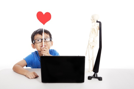 Cute asian boy holding heart shape with laptop and human skeleton photo