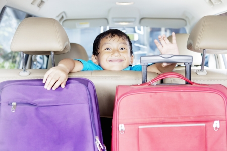 inside car: Asian boy with two traveling bags in the car Stock Photo