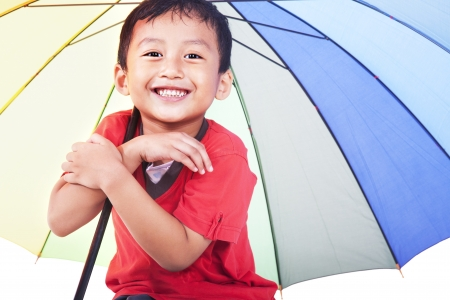 sotto la pioggia: Colpo di carino ragazzo asiatico sorridente sotto l'ombrello multicolore. girato in studio Archivio Fotografico