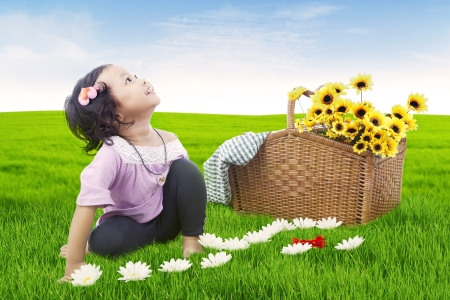 Cute asian girl with basket of sunflowers. shot outdoor photo