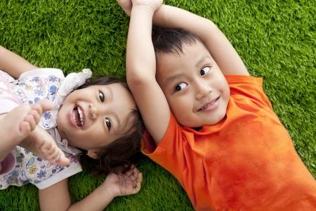 hermanos jugando: Lindos los hermanos felices asiático que yacen en la hierba verde prado de disparos