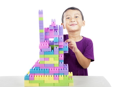 Cute little boy smiling behind building of lego blocks shot in studio isolated on white photo