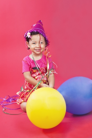 Cute little girl with colorful balloons on a red background, shot in studio photo