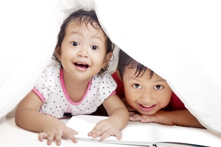 two face: Cute asian siblings reading book under blanket. shot in studio Stock Photo