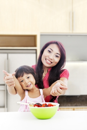 Happy mother and daughter with fruit salad showing thumbs-up. shot in the kitchen  photo