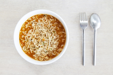 cooked instant noodle: Closeup of homemade instant noodles on a bowl with fork and spoon