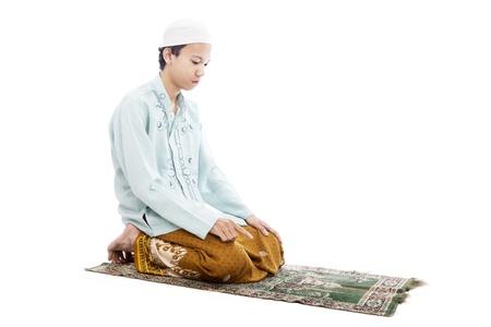 islamic prayer: Portrait of asian muslim man praying on mat. shot in studio isolated on white