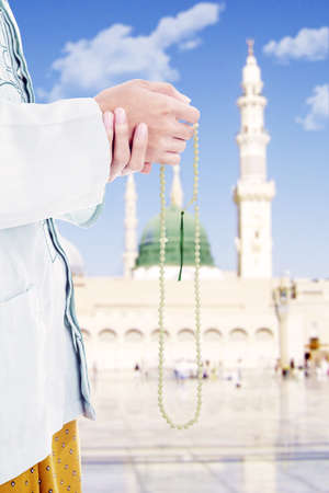 moslem: Close up of asian muslim holding prayer beads in front of mosque. Shot at mosque during Ramadan  Stock Photo