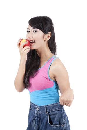 Weight loss concept: Asian woman wearing her huge old jeans and eating apple photo