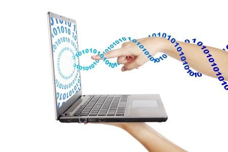 codigo binario: Mano que señala en la pantalla del ordenador portátil con código binario flujo hacia fuera de la computadora portátil