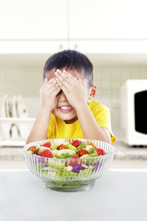 Boy refuses to eat a big portion of salad by cover his eyes. shot in the kitchen photo