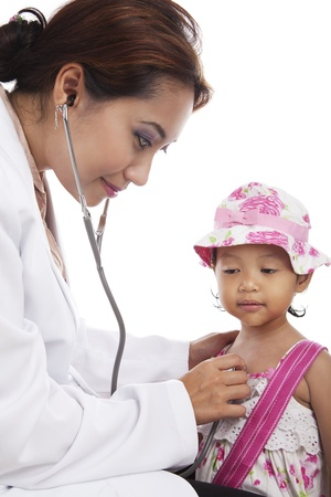 workplace wellness: A young doctor examining child with stethoscope at medical office