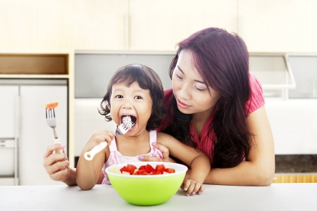 Asian young mother helping her daughter eats fresh fruit salad. shot in the kitchen Imagens