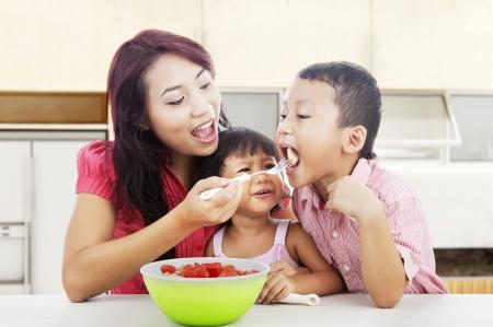 ni�os comiendo: Madre y ni�os que comen el bocado sano - ensalada de frutas. Rodada en la cocina Foto de archivo