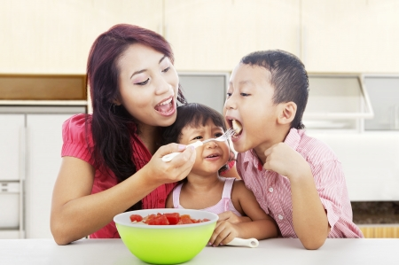 indonesian woman: Mother and children eating healthy snack - fruit salad. Shot in the kitchen