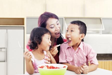 family eating: Madre y ni�os comiendo bocadillos saludables - ensalada de frutas. Herido de bala en la cocina