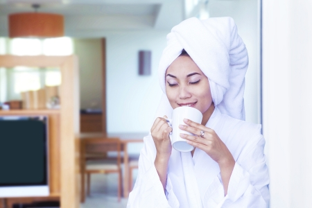 Asian woman wearing bathrobe enjoying cup of coffee at hotel room Stock Photo - 14683847