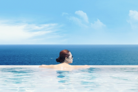 Young asian woman in the swimming pool near the ocean enjoying the ocean view photo