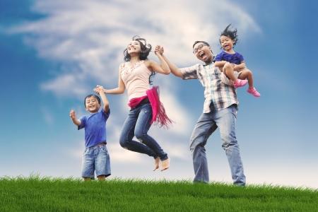 Opgewonden en gelukkig Aziatische familie springen in weide neergeschoten tijdens de zomer