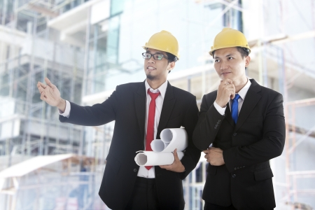 Young architects wearing a protective helmet standing in front of a building site.  photo