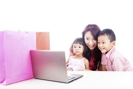 Happy asian family shopping online by using laptop computer, isolated on white photo