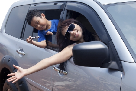 trip: Family travelling by car, mother waving with hands Stock Photo