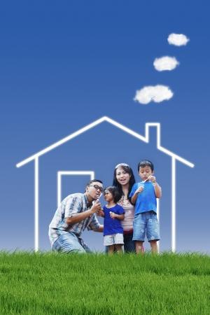 Dream Home: Portrait der asiatischen Familie mit Traumhaus spielen Blase im Freien