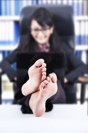 Businesswoman using laptop with Feet Up on a Table, shot in the office photo