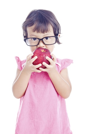 Portrait of asian female preschooler eating red apple on white background photo